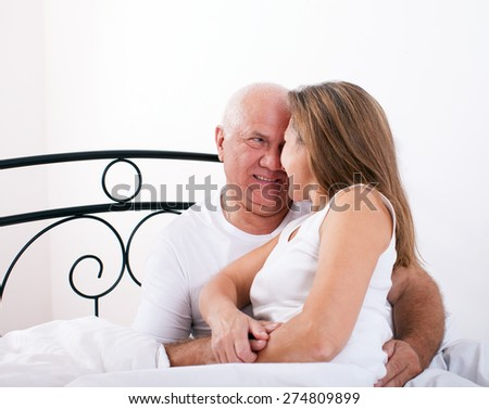 Senior  man and   woman resting on   bed in   embrace. - stock photo