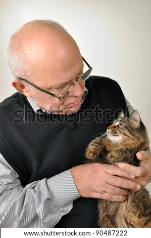 senior man wearing glasses with a cat - stock photo