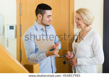 Senior woman questionnaire for marketing worker or employee of the company at door - stock photo