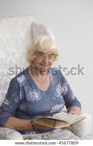 Senior woman reading book sitting on chair