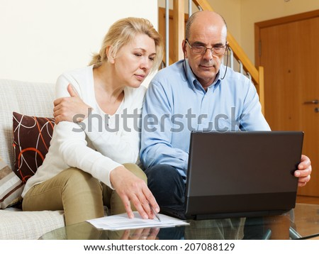 serious mature couple  looking documents in laptop in home interior - stock photo