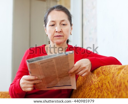 serious mature woman with newspaper at home - stock photo