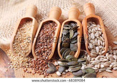 Sesame, flax, pumpkin and sunflower seeds in wooden spoons - stock photo