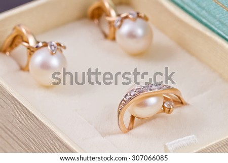 set of gold earrings and rings with pearls lies in a gift box - stock photo