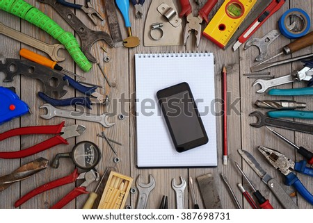 Set of tools on a wooden floor with a notebook and a mobile phone in the centre.                          - stock photo