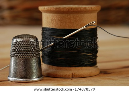 Sewing still life of antique thimble with wooden spool of thread and vintage needle on wood background.  Macro with shallow dof.  Selective focus on thimble and eye of needle. - stock photo