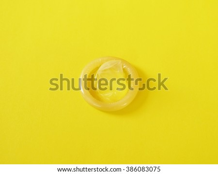 Sex concept. Condom on yellow background - stock photo