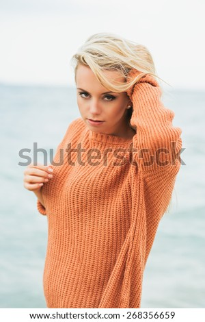 sexy girl poses on a beach. beautiful blonde enjoys walk on the coast - stock photo