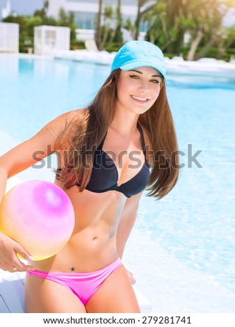 Sexy sportive girl having fun in swimming pool  with ball, enjoying luxury beach resort, active summer vacation, sport and enjoyment concept - stock photo