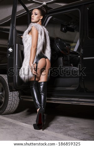 sexy woman in lingerie and fur coat posing beside a car - stock photo