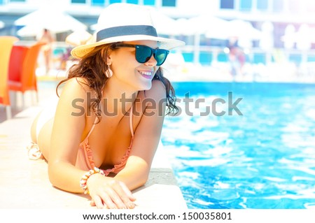 sexy woman in pink bikini enjoying the sunset on tropical swimming pool - stock photo