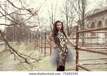 Sexy woman near a stable in a trendy gold necklace - stock photo