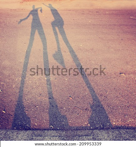 shadow of two people play fighting in the street toned with a retro vintage instagram filter  - stock photo