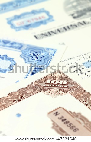 100 shares. Old stock share certificate. Vintage scripophily objects. Shallow depth of field. - stock photo