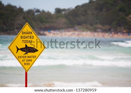 Shark warning sign on the beach - stock photo