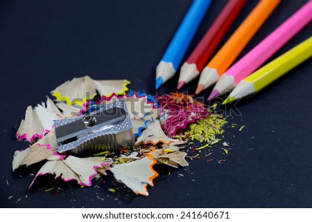 Sharpened Colorful Pencils Coming from Corner, Metallic Pencil Sharpener and Colorful Pencil Shavings on Black Background - stock photo