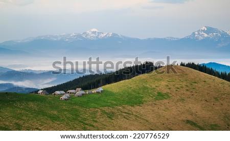 Shepherd's huts against Ukrainian Carpathian mountains - stock photo