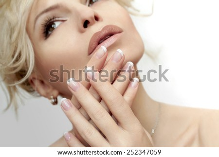 Short French manicure on hands of a young woman. - stock photo