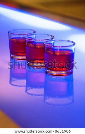 3 shot glasses on a bar - stock photo