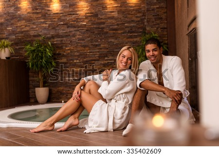 Shot of a couple posing together at the spa. High ISO, grainy image, selective focus. - stock photo