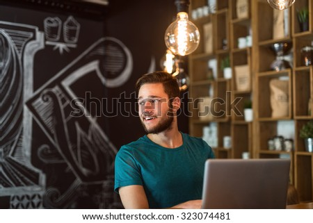 Shot of a young man working on a laptop in a cafe. Selective focus, natural light, higher ISO. - stock photo