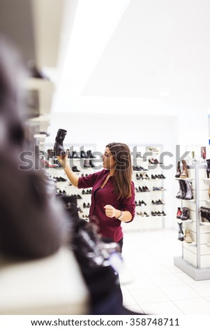 Shot of an attractive and stylish young woman looking at shoes in a clothing store. - stock photo