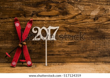 2017 sign happy new year, retro vintage aged skiing with ski poles stand on wooden table or board background. empty copy space for inscription or other objects