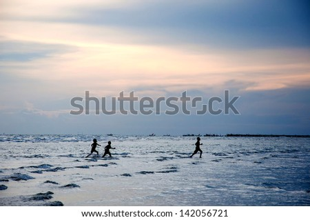 silhouette children playing in the water - stock photo