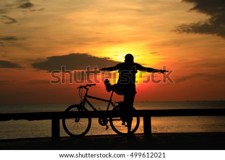 silhouette man and Bicycle on the beach with sunrise sky background,