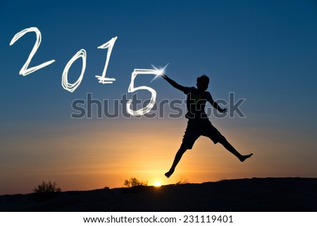 2015 Silhouette of a boy jumping in the sun - stock photo