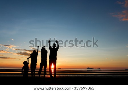 Silhouette of a man and his son playing together on the beach at sunset.
