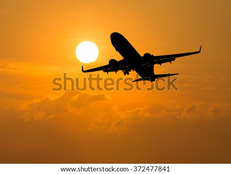 silhouette of an airplane at sunset - stock photo