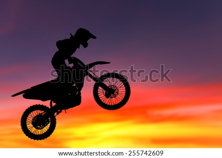 silhouette of biker jumping on the light in the evening.