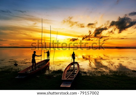 silhouette of children on wood boat at sunset - stock photo