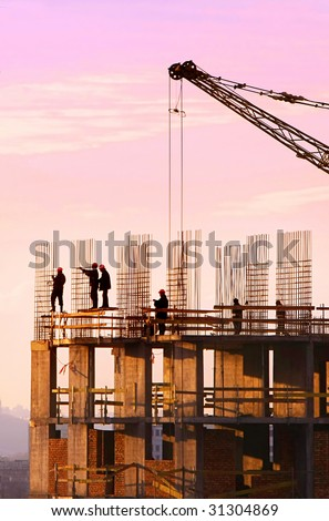 Silhouette of construction workers - stock photo