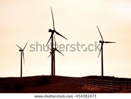 Silhouette of wind turbines in the hills of Southwest Oklahoma . - stock photo