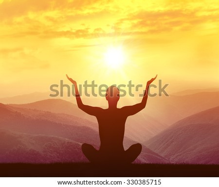Silhouette of yoga man in the mountains at sunrise