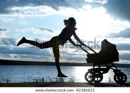 Silhouette of young slim mother doing exercise with a pram - stock photo