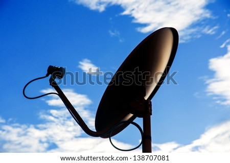 silhouette Satellite dish againts blue sky - stock photo