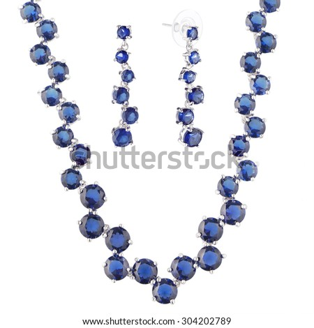 silver metal necklace and earrings  with blue crystal, isolated on white background