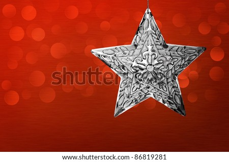 Silver Star Christmas Ornament Over Red Brushed Metal Background With LED Bokeh Lights