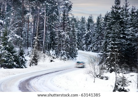 single car driving along a a winter road - stock photo