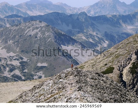 Single Woman High On A Rocky Mountain Peak         - stock photo