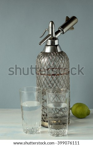 Siphon and two glasses with soda water on a gray-blue background - stock photo
