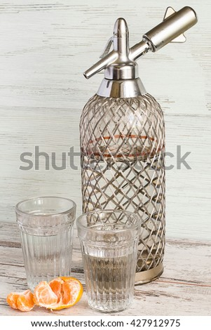 Siphon and two glasses with soda water on a light wooden background. - stock photo