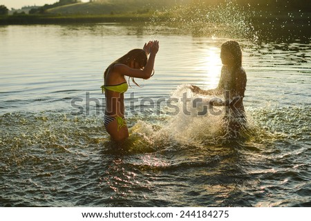 2 sisters girlfriends having fun playing together in the lake at sunset - stock photo