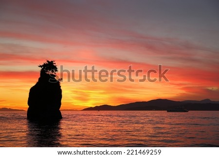 Siwash Rock Sunset, English Bay, Vancouver. Sunset over English Bay silhouetting Siwash Rock in Stanley Park. Vancouver, British Columbia, Canada.  - stock photo