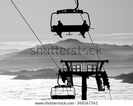 Ski lift chairs on winter day over the clouds, cableway chair equipment sport skiing background /  silhouette of skiers on mountain hill  - stock photo