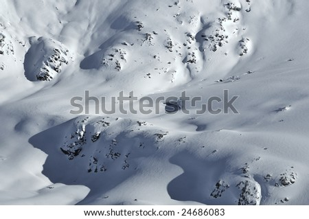 4 skiers on a glacier covered with fresh snow, in the mountains ski past an open crevasse. - stock photo