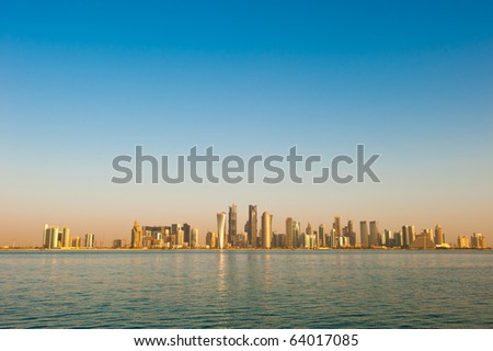 2010 Skyline of the arabian city of Doha in Qatar, captured in the very early morning with the rich warm colours from the sun reflecting off the glass skyscrapers. - stock photo